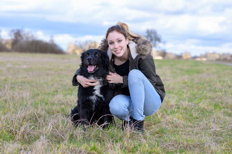 Ευτυχής νέα γυναίκα που αγκαλιάζει το αγαπημένο μαύρο σκυλί της στοκ φωτογραφίες