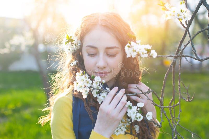 Ευτυχής νέα γυναίκα που απολαμβάνει τα λουλούδια μυρωδιάς πέρα από το υπόβαθρο κήπων άνοιξη στοκ εικόνα