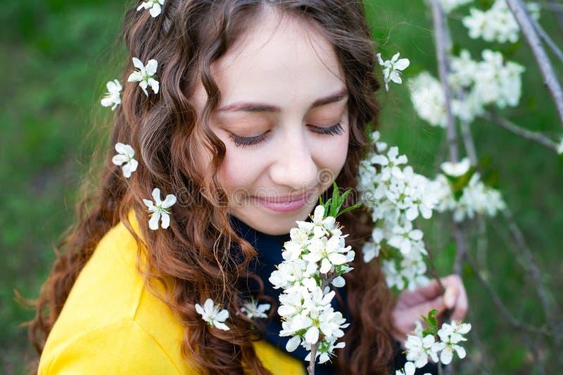 Ευτυχής νέα γυναίκα που απολαμβάνει τα λουλούδια μυρωδιάς πέρα από το υπόβαθρο κήπων άνοιξη στοκ φωτογραφίες με δικαίωμα ελεύθερης χρήσης