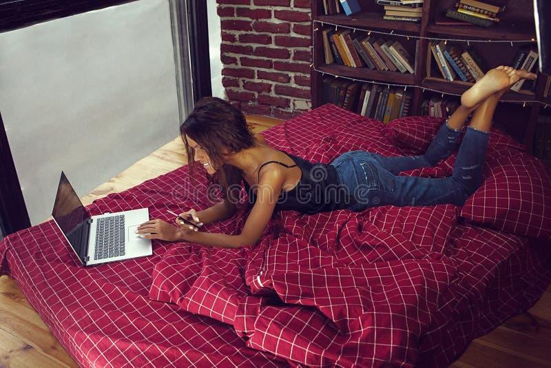 Ευτυχής νέα γυναίκα που βάζει στο ντιβάνι και που χρησιμοποιεί το lap-top στο διαμέρισμα σοφιτών - εικόνα στοκ φωτογραφίες