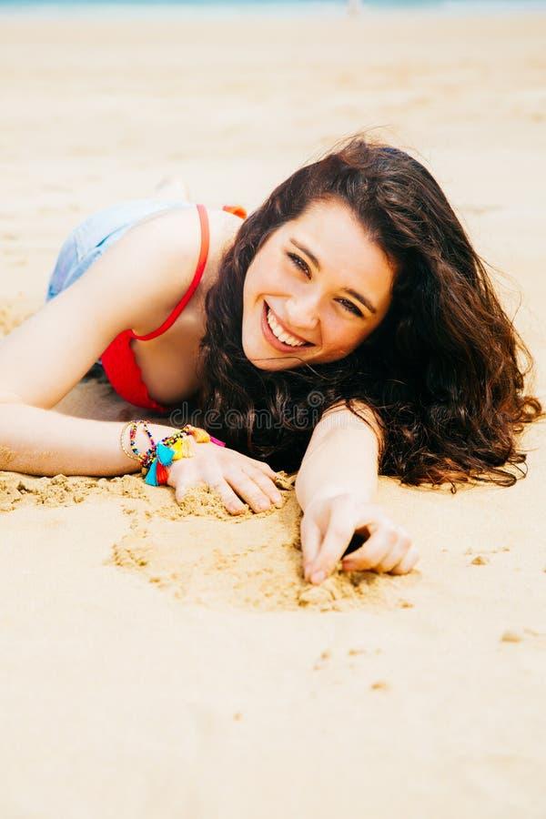 Ευτυχής νέα γυναίκα που βρίσκεται στην παραλία στοκ εικόνες με δικαίωμα ελεύθερης χρήσης