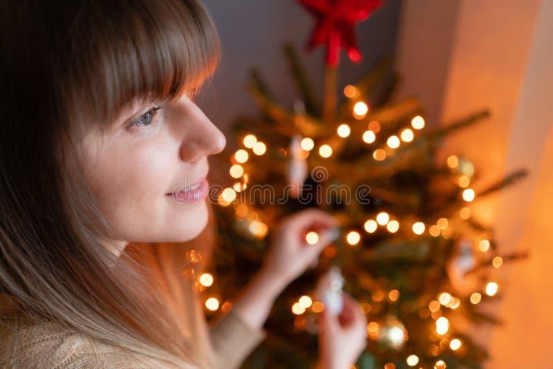 Ευτυχής νέα γυναίκα που διακοσμεί το χριστουγεννιάτικο δέντρο στο σπίτι Χειμερινές διακοπές σε ένα εσωτερικό σπιτιών Χρυσά και άσ στοκ εικόνες