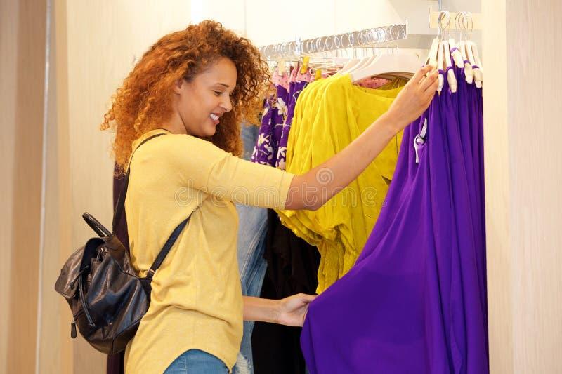 Ευτυχής νέα γυναίκα που εξετάζει τα ενδύματα στο κατάστημα στοκ φωτογραφία