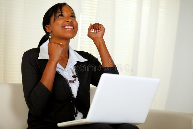 Ευτυχής νέα γυναίκα που εργάζεται στο lap-top και που ανατρέχει στοκ φωτογραφία