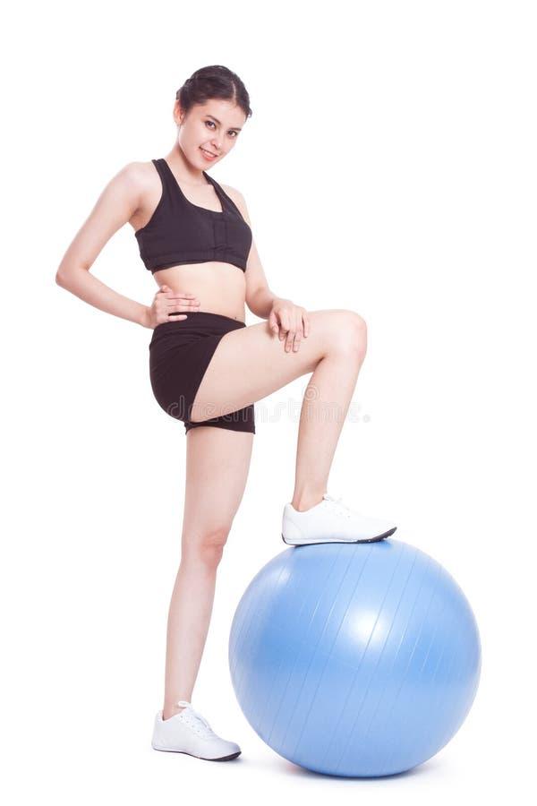 Ευτυχής νέα γυναίκα που κάνει τις ασκήσεις με τη σφαίρα ικανότητας στοκ φωτογραφία