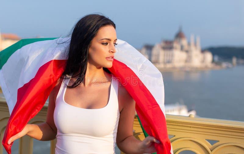 Ευτυχής νέα γυναίκα που καλύπτεται από την ουγγρική σημαία στη Βουδαπέστη στοκ εικόνες