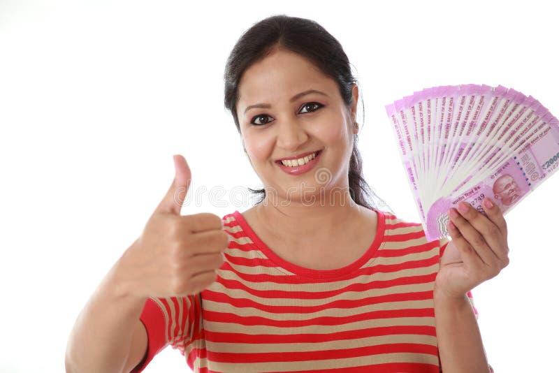 Ευτυχής νέα γυναίκα που κρατά τις ινδικές σημειώσεις ρουπίων του 2000 στοκ φωτογραφία με δικαίωμα ελεύθερης χρήσης