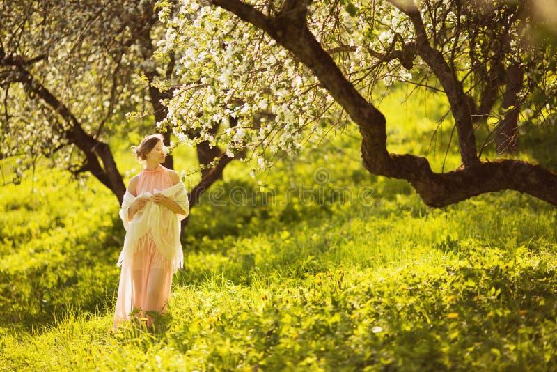 Ευτυχής νέα γυναίκα που μυρίζει ένα λουλούδι σε ένα δέντρο μηλιάς στοκ εικόνες