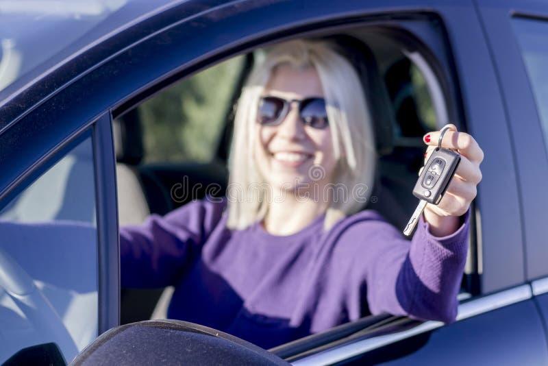 Ευτυχής νέα γυναίκα που παρουσιάζει κλειδιά από το πρώτο αυτοκίνητό της - πλάγια όψη στοκ εικόνες