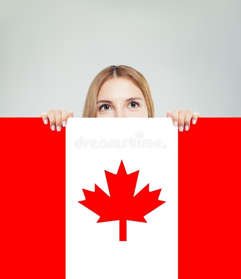 Ευτυχής νέα γυναίκα που παρουσιάζει υπόβαθρο σημαιών του Καναδά Ζήστε, εργαστείτε στοκ εικόνες
