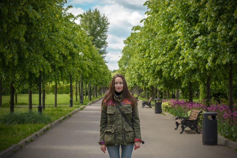 Ευτυχής νέα γυναίκα που περπατά στο θερινό πάρκο στοκ εικόνες
