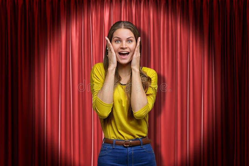 Ευτυχής νέα γυναίκα που στέκεται και που εξετάζει τη κάμερα με τα χέρια στο πρόσωπο, στο επίκεντρο, ενάντια στην κόκκινη σκηνική  στοκ εικόνες
