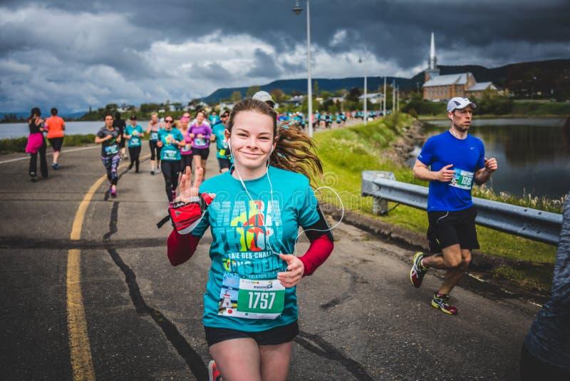 Ευτυχής νέα γυναίκα που τρέχει 10K και που ακούει κάποια μουσική στοκ φωτογραφία με δικαίωμα ελεύθερης χρήσης