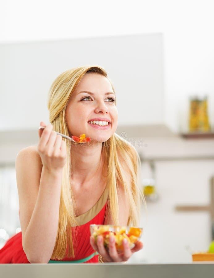 Ευτυχής νέα γυναίκα που τρώει τη σαλάτα νωπών καρπών στην κουζίνα στοκ φωτογραφίες