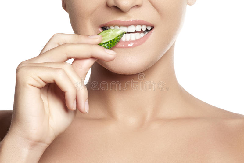 Ευτυχής νέα γυναίκα που τρώει το αγγούρι Υγιές χαμόγελο με τα άσπρα δόντια στοκ φωτογραφία