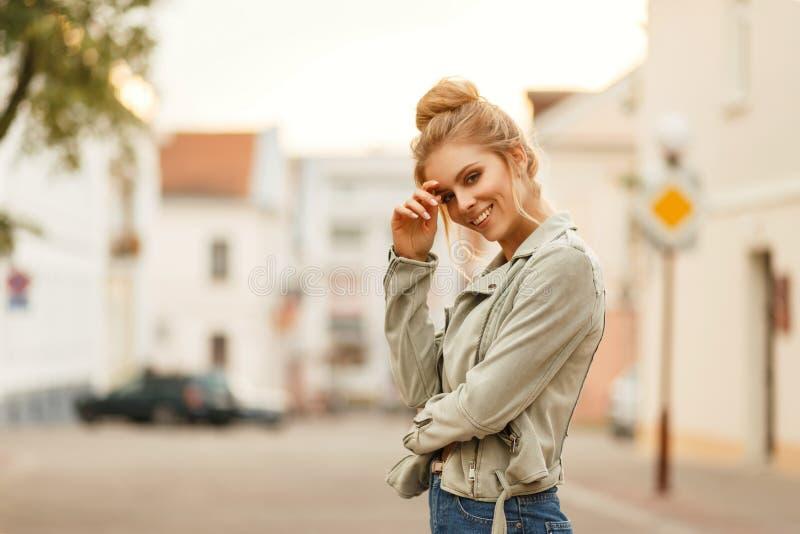 Ευτυχής νέα γυναίκα που χαμογελά σε ένα μοντέρνο σακάκι στην πόλη στοκ εικόνες