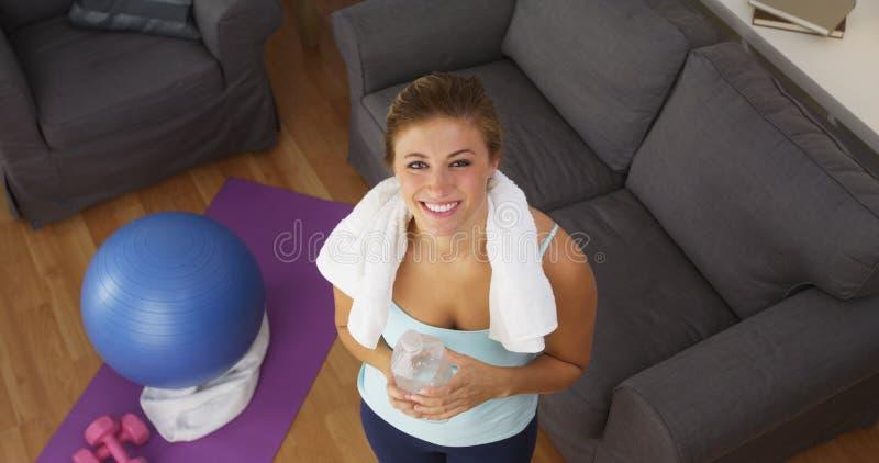 Ευτυχής νέα γυναίκα που χαμογελά μετά από να ασκήσει στοκ φωτογραφίες