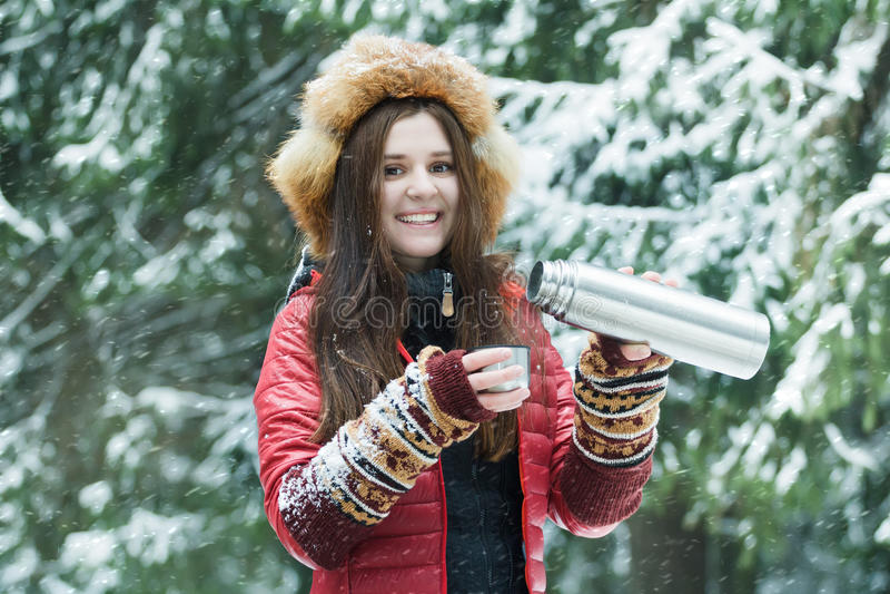 Ευτυχής νέα γυναίκα που χύνει το ζεστό ποτό από τη ματ κενή φιάλη τουριστών στο μεταλλικό φλυτζάνι στο χειμερινό δάσος στοκ φωτογραφία