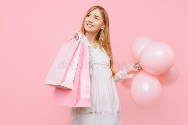 Ευτυχής νέα γυναίκα, σε ένα άσπρο φόρεμα, με τις τσάντες στα χέρια και τα μπαλόνια, σε ένα ρόδινο υπόβαθρο ψωνίζοντας λευκή γυναί στοκ φωτογραφίες