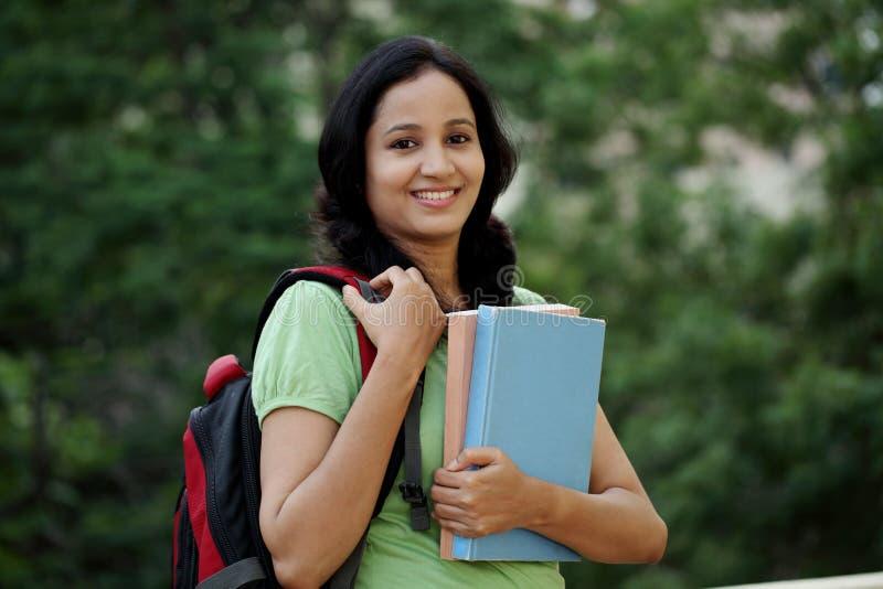Ευτυχής νέα γυναίκα σπουδαστής στην πανεπιστημιούπολη κολλεγίων στοκ εικόνες