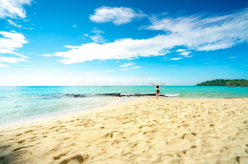 Ευτυχής νέα γυναίκα στα άσπρα πουκάμισα και τα σορτς που περπατά στην παραλία άμμου Χαλάρωση και απόλαυση των διακοπών στην τροπι στοκ εικόνες