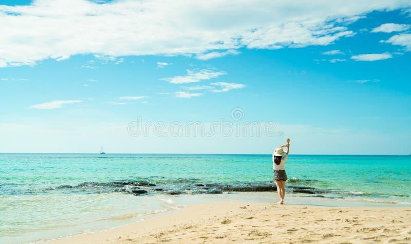 Ευτυχής νέα γυναίκα στα άσπρα πουκάμισα και τα σορτς που περπατά στην παραλία άμμου Χαλάρωση και απόλαυση των διακοπών στην τροπι στοκ φωτογραφίες με δικαίωμα ελεύθερης χρήσης