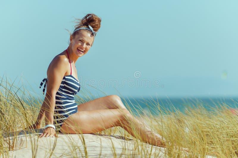 Ευτυχής νέα γυναίκα στη ριγωτή συνεδρίαση μαγιό στην ακτή στοκ εικόνα