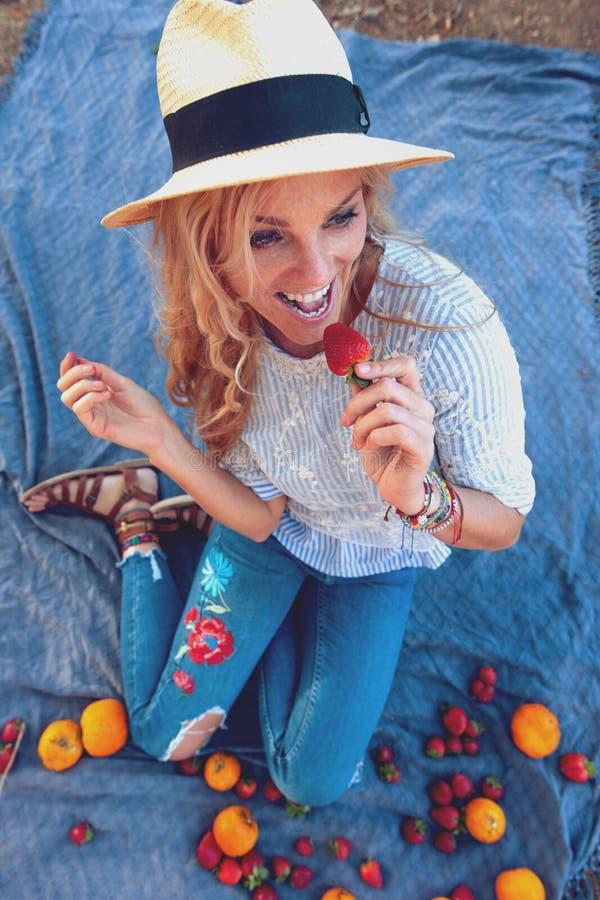 Ευτυχής νέα γυναίκα στο καπέλο που τρώει τη φράουλα στο πικ-νίκ στοκ φωτογραφία με δικαίωμα ελεύθερης χρήσης