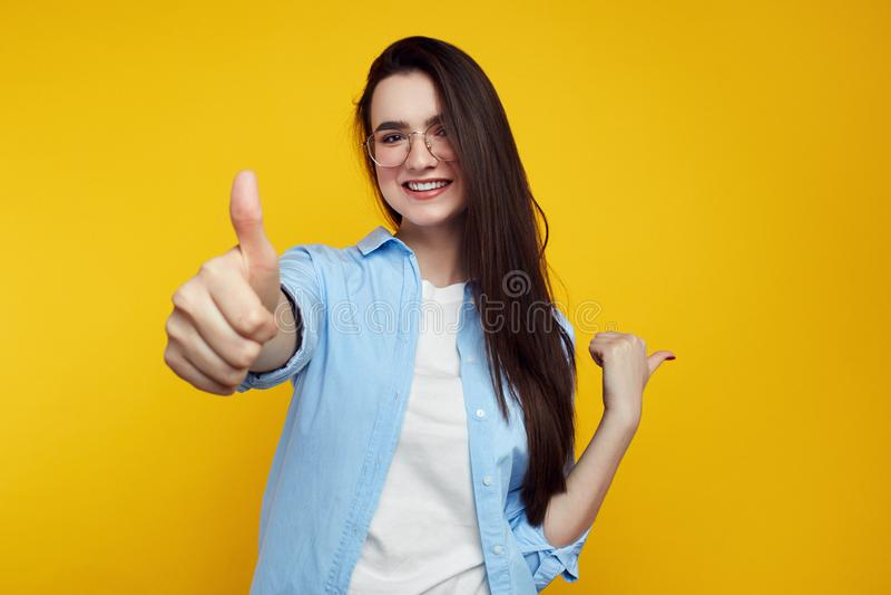 Ευτυχής νέα γυναίκα στο μπλε πουκάμισο και eyeglasses που δείχνουν μακριά και που παρουσιάζουν αντίχειρα στον πορτοκαλή τοίχο στοκ φωτογραφίες με δικαίωμα ελεύθερης χρήσης