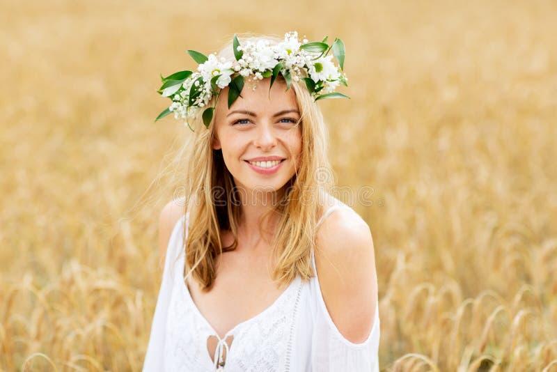 Ευτυχής νέα γυναίκα στο στεφάνι λουλουδιών στον τομέα δημητριακών στοκ εικόνα