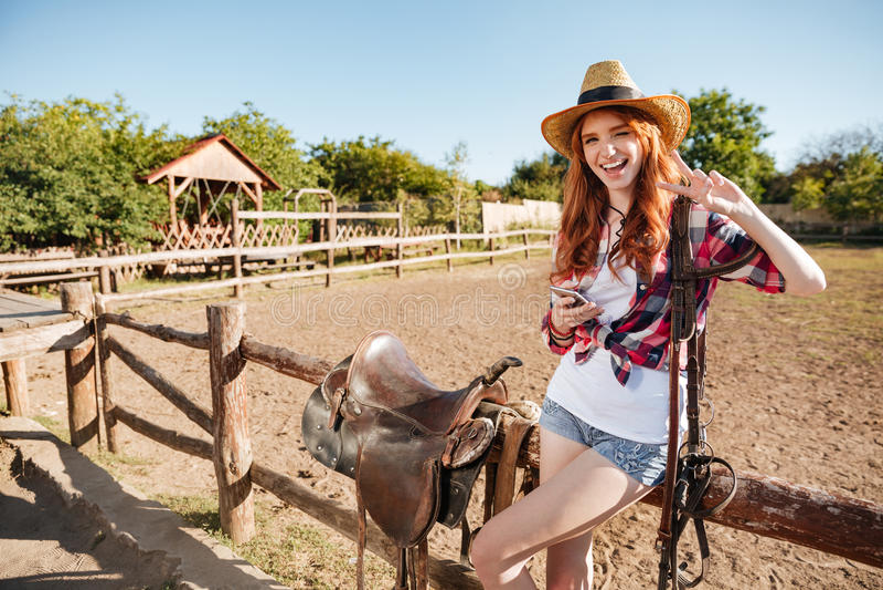 Ευτυχής νέα γυναίκα cowgirl με το τηλέφωνο κυττάρων που παρουσιάζει σημάδι ειρήνης στοκ εικόνες