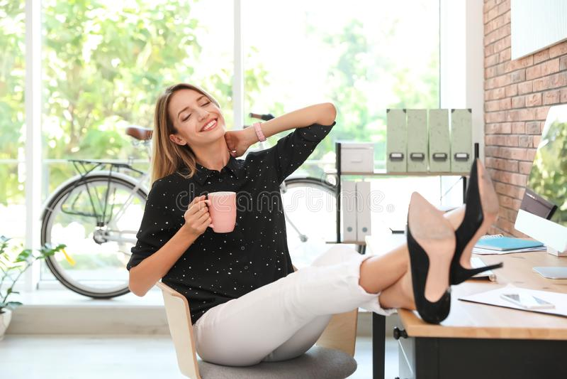 Ευτυχής νέα επιχειρηματίας με το φλιτζάνι του καφέ που απολαμβάνει την ειρηνική στιγμή στοκ φωτογραφία