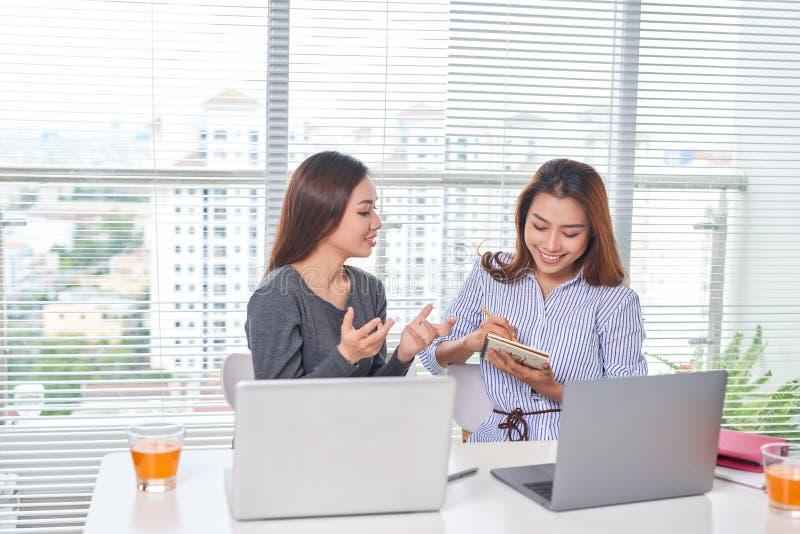 Ευτυχής νέα επιχειρηματίας που μιλά στο συνάδελφό της στοκ εικόνα