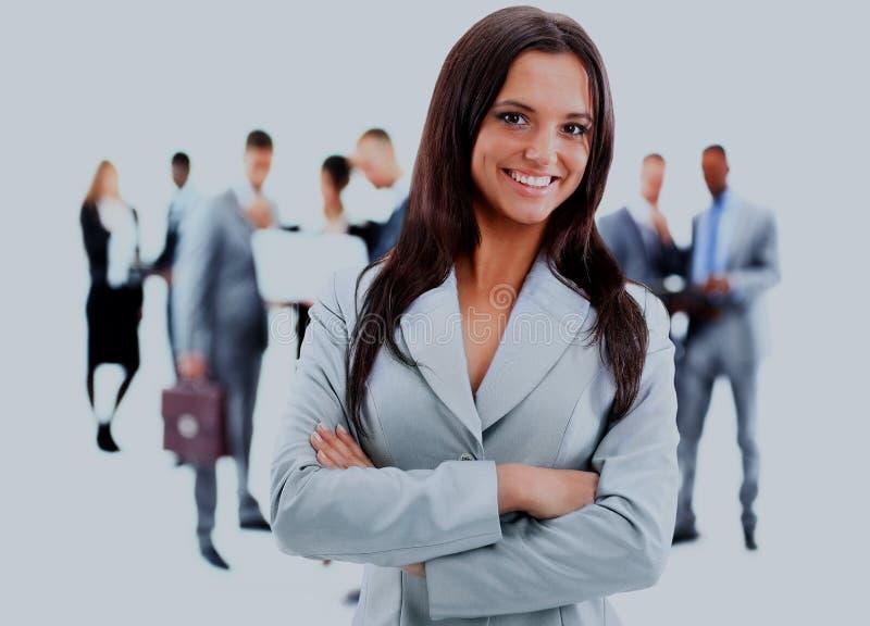 Ευτυχής νέα επιχειρησιακή γυναίκα που στέκεται μπροστά από την ομάδα της στοκ φωτογραφίες
