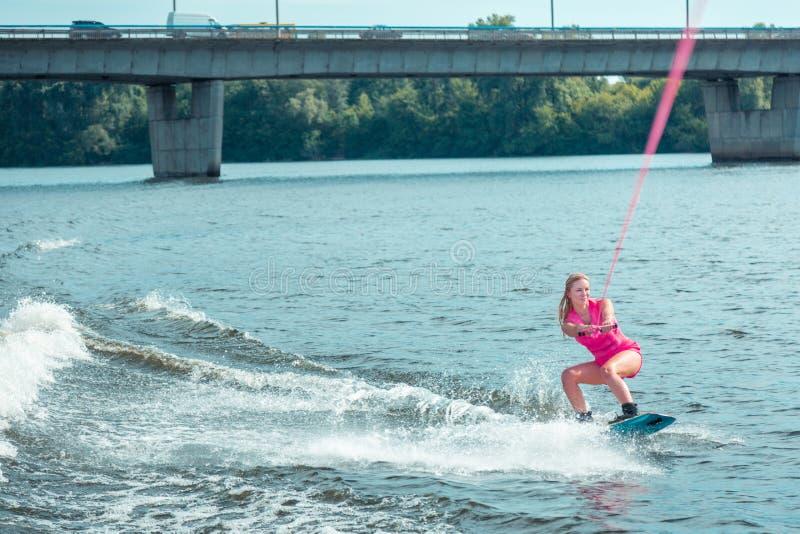Ευτυχής νέα καυκάσια ξανθή γυναίκα που οδηγά ένα wakeboard στοκ εικόνες