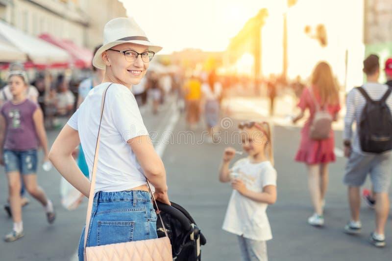 Ευτυχής νέα καυκάσια φαλακρή γυναίκα στο καπέλο και τα περιστασιακά ενδύματα που απολαμβάνει τη ζωή μετά από τον επιζόντα καρκίνο στοκ εικόνες