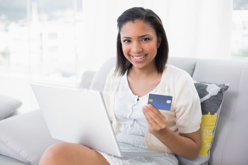 Ευτυχής νέα μελαχροινή μαλλιαρή γυναίκα στα άσπρα ενδύματα που ψωνίζει on-line με ένα lap-top στοκ εικόνες με δικαίωμα ελεύθερης χρήσης
