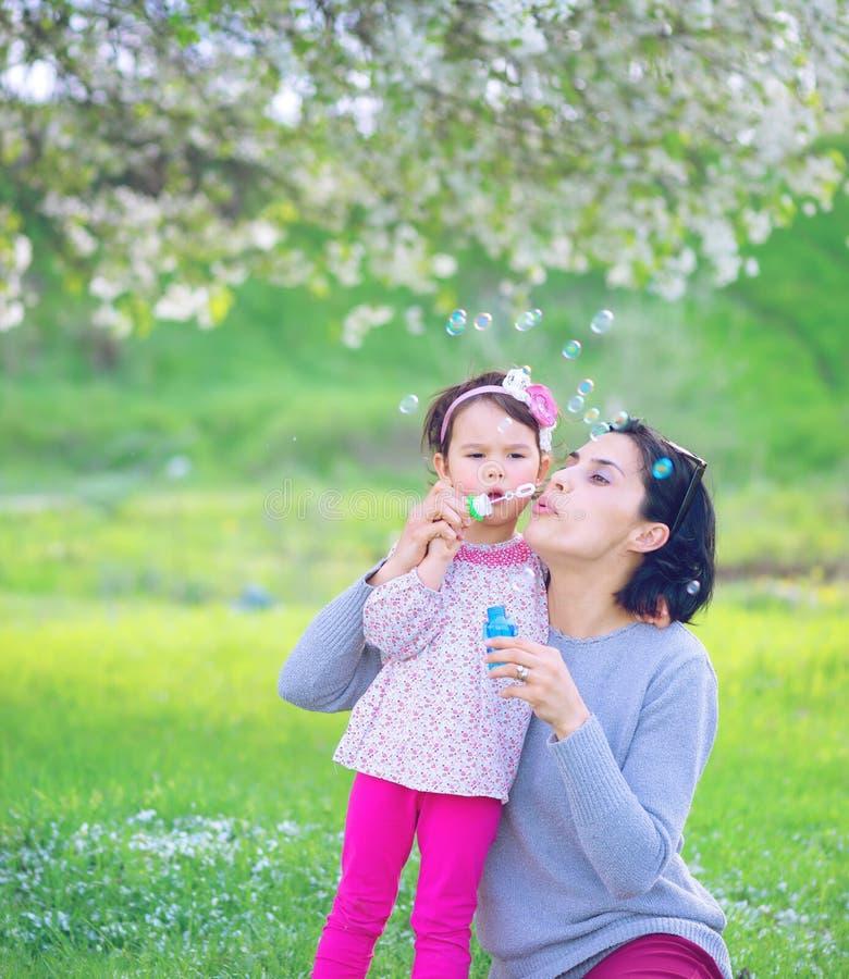 Ευτυχής νέα μητέρα και οι φυσώντας φυσαλίδες σαπουνιών κορών της στοκ εικόνα με δικαίωμα ελεύθερης χρήσης