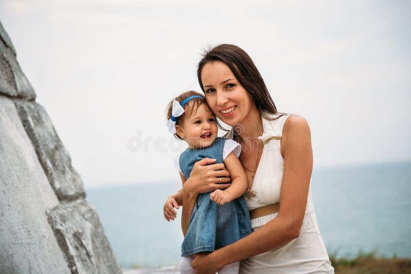 Ευτυχής νέα μητέρα με μια μικρή κόρη στα χέρια που αγκαλιάζει πλησίον στο φάρο, υπαίθρια υπόβαθρο στοκ φωτογραφία