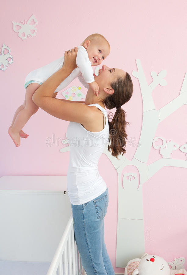 Ευτυχής νέα μητέρα που ανυψώνει το χαριτωμένο μωρό από το παχνί στοκ εικόνες