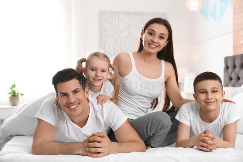 Ευτυχής νέα οικογένεια μαζί στο κρεβάτι στοκ φωτογραφία με δικαίωμα ελεύθερης χρήσης