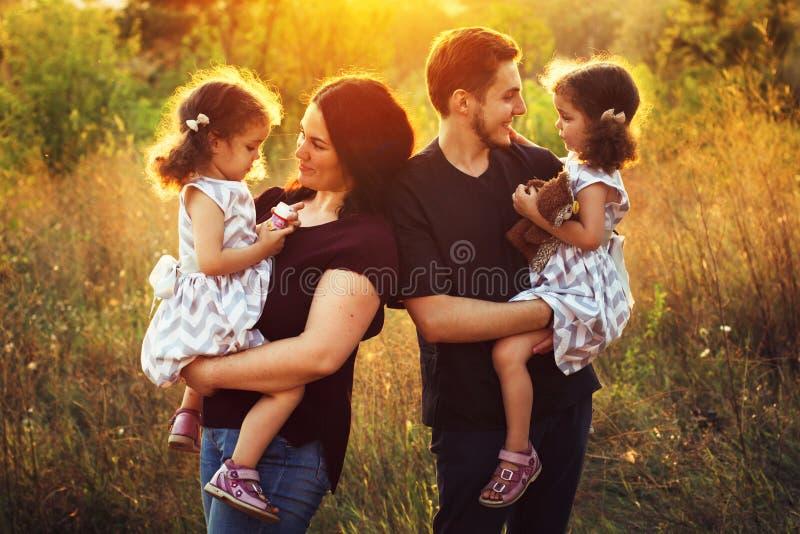 Ευτυχής νέα οικογένεια με δύο παιδιά υπαίθρια δίδυμα κοριτσιών στοκ φωτογραφία