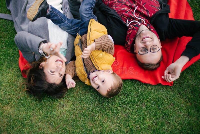Ευτυχής νέα οικογένεια, μητέρα πατέρων και γιος στο πικ-νίκ υπαίθρια στοκ εικόνα με δικαίωμα ελεύθερης χρήσης