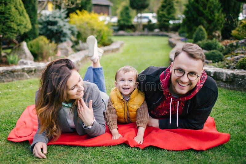 Ευτυχής νέα οικογένεια, μητέρα πατέρων και γιος στο πικ-νίκ υπαίθρια στοκ φωτογραφίες