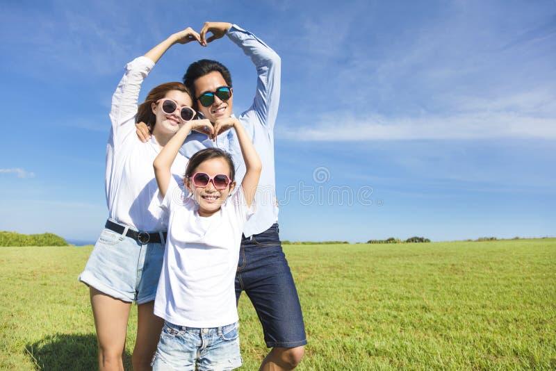 Ευτυχής νέα οικογένεια που διαμορφώνει τη μορφή αγάπης στοκ εικόνες