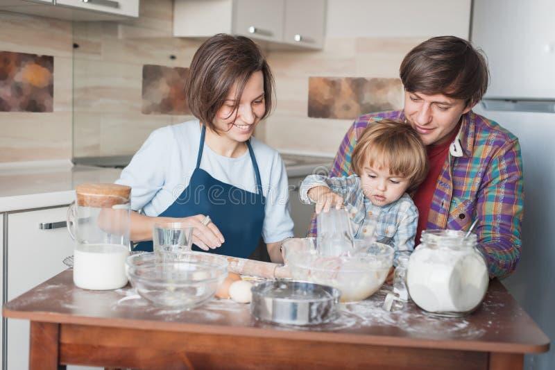 ευτυχής νέα οικογένεια που προετοιμάζει τη ζύμη για τα μπισκότα στοκ φωτογραφία με δικαίωμα ελεύθερης χρήσης