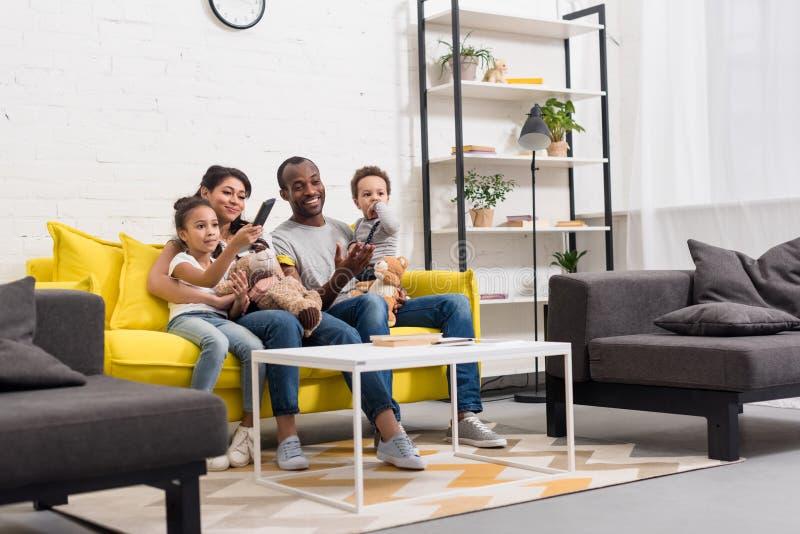 ευτυχής νέα οικογένεια που προσέχει τη TV από κοινού στοκ εικόνες