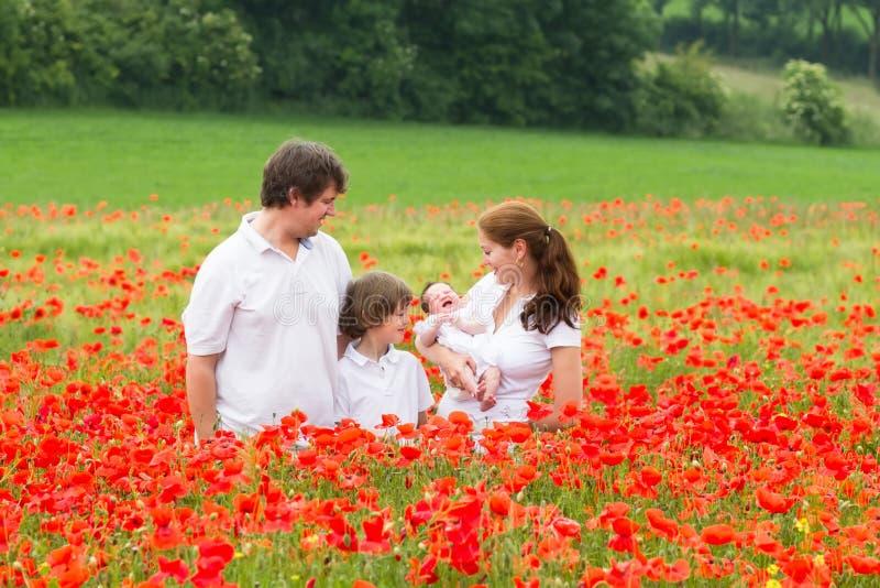Ευτυχής νέα οικογένεια που στέκεται στον τομέα λουλουδιών παπαρουνών στοκ εικόνες
