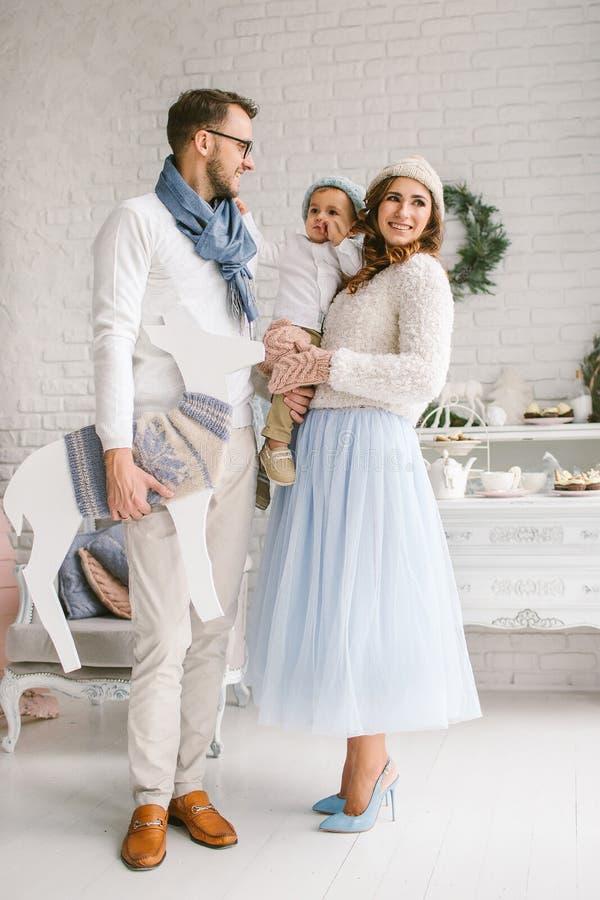 Ευτυχής νέα οικογένεια που χαμογελά και που αγκαλιάζει στο φωτεινό στούντιο σοφιτών στοκ εικόνες
