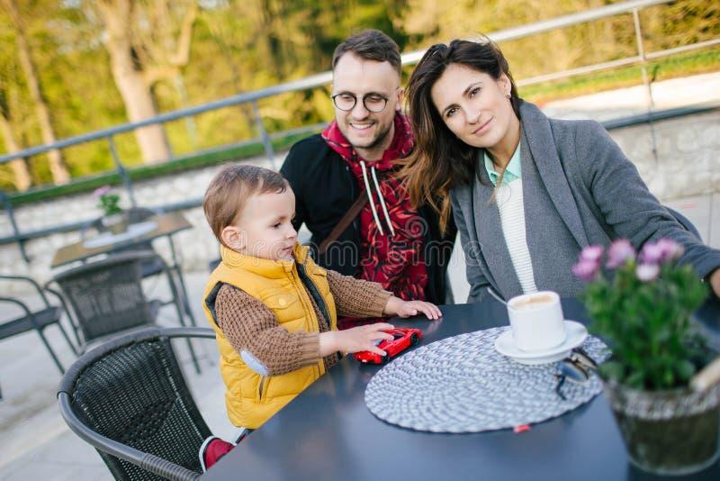 Ευτυχής νέα οικογένεια στον καφέ υπαίθρια την ηλιόλουστη ημέρα στοκ εικόνες